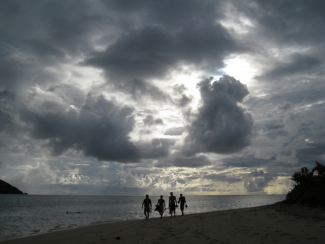 surfers walking home with big clouds above