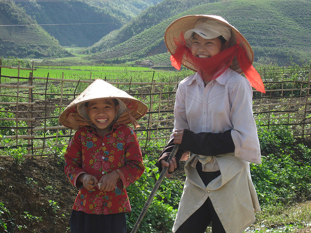 laughing girls with traditional conical hats near Sapa, Vietnam