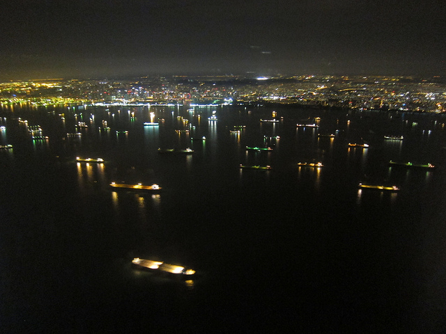many cargo ships at night seen from a plane