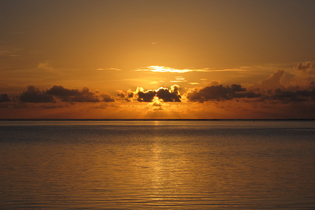 orange sunset with sun behind clouds on the island of Moorea