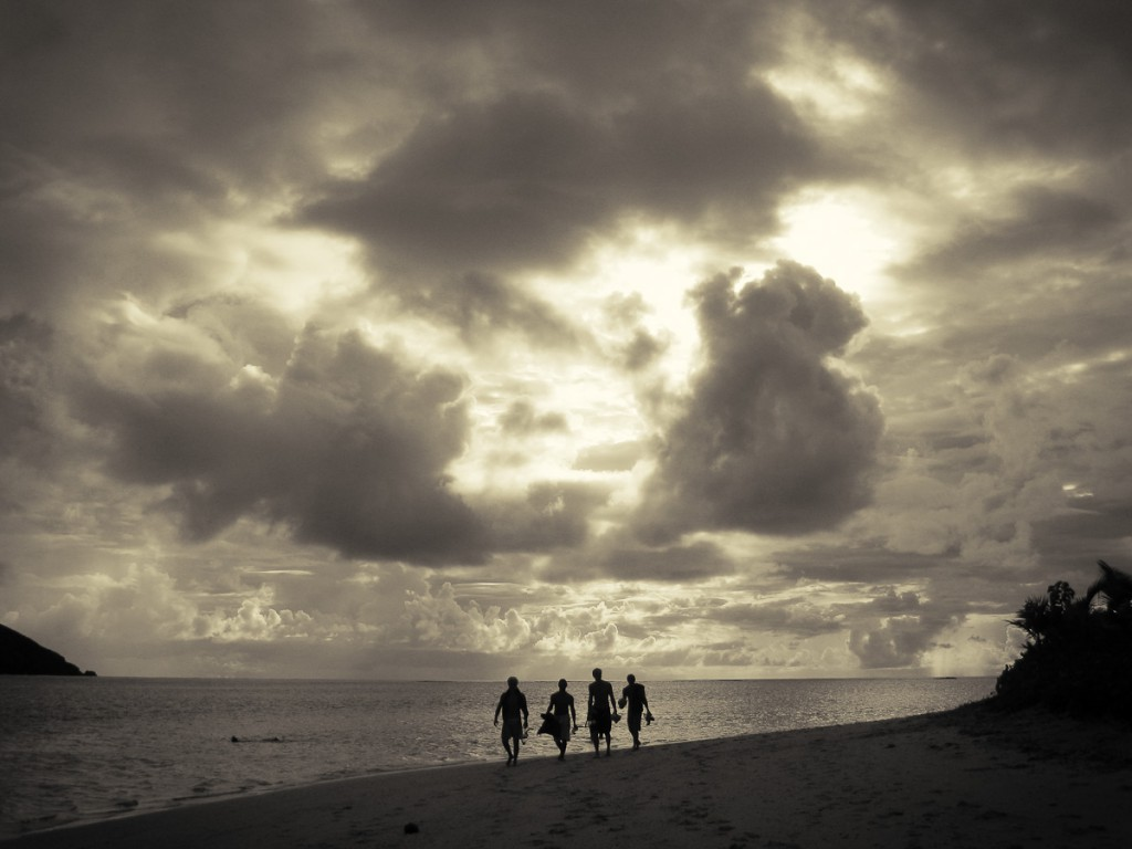 dramatic clouds behind surfers walking on the beach in Fiji