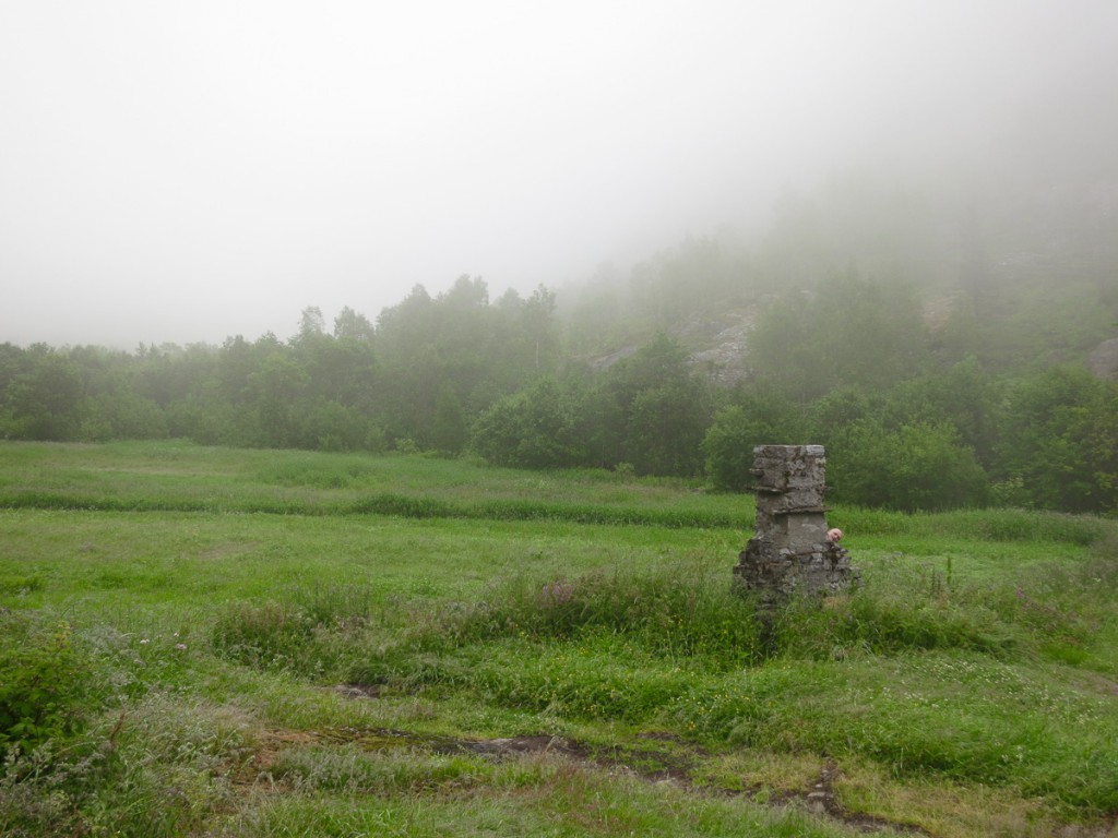 man hiding behind old chimney in foggy green field