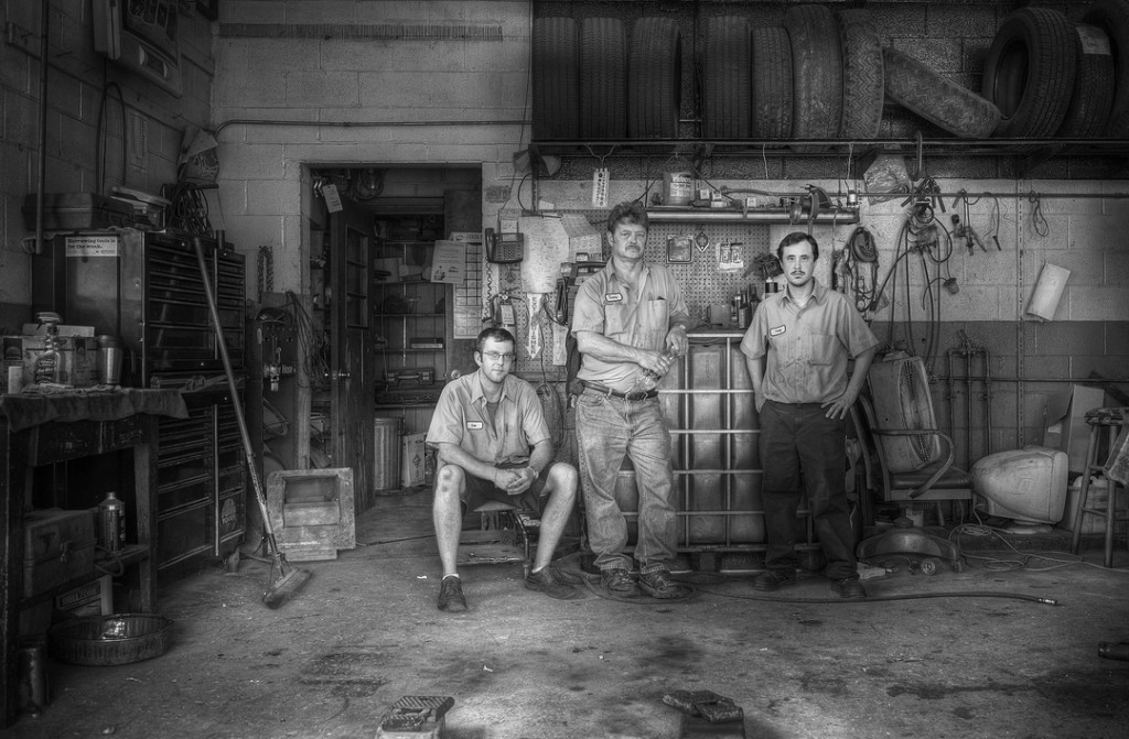 black and white photo of three auto mechanics