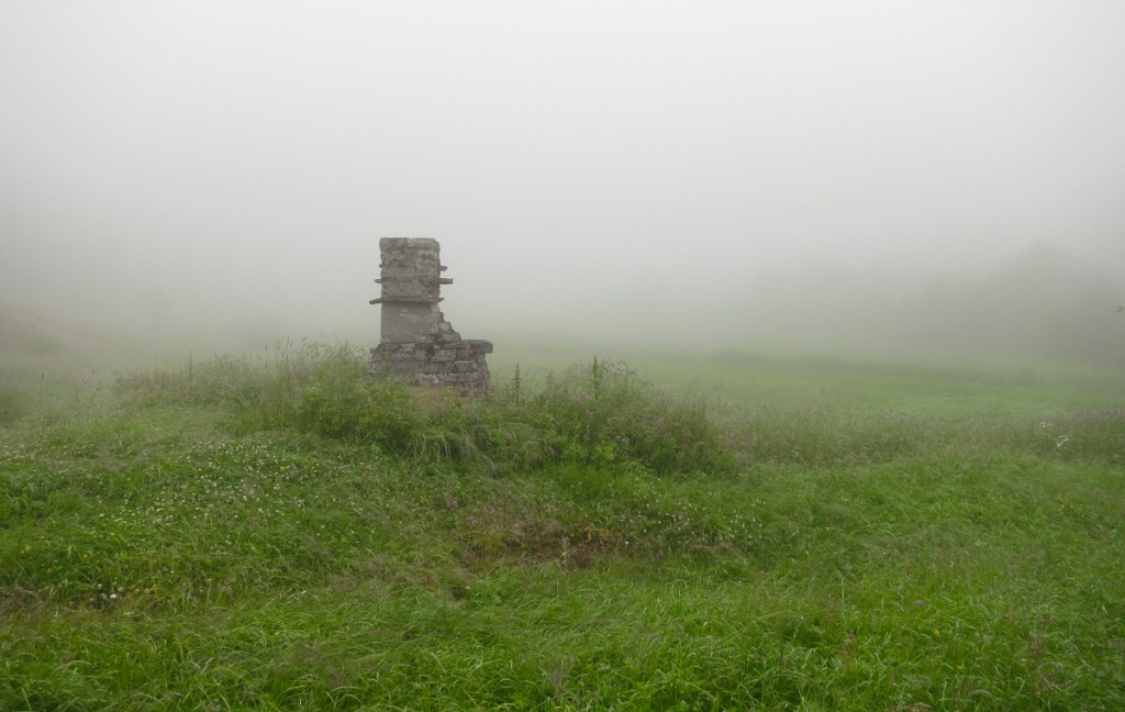 foggy green field with old chimney